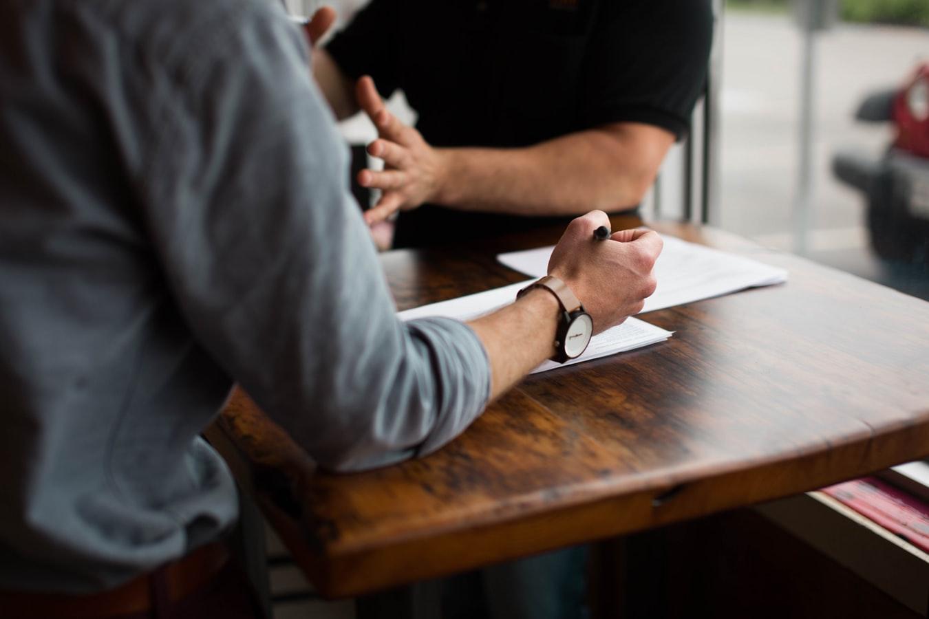 Un candidat écrivant une lettre de motivation sur une table