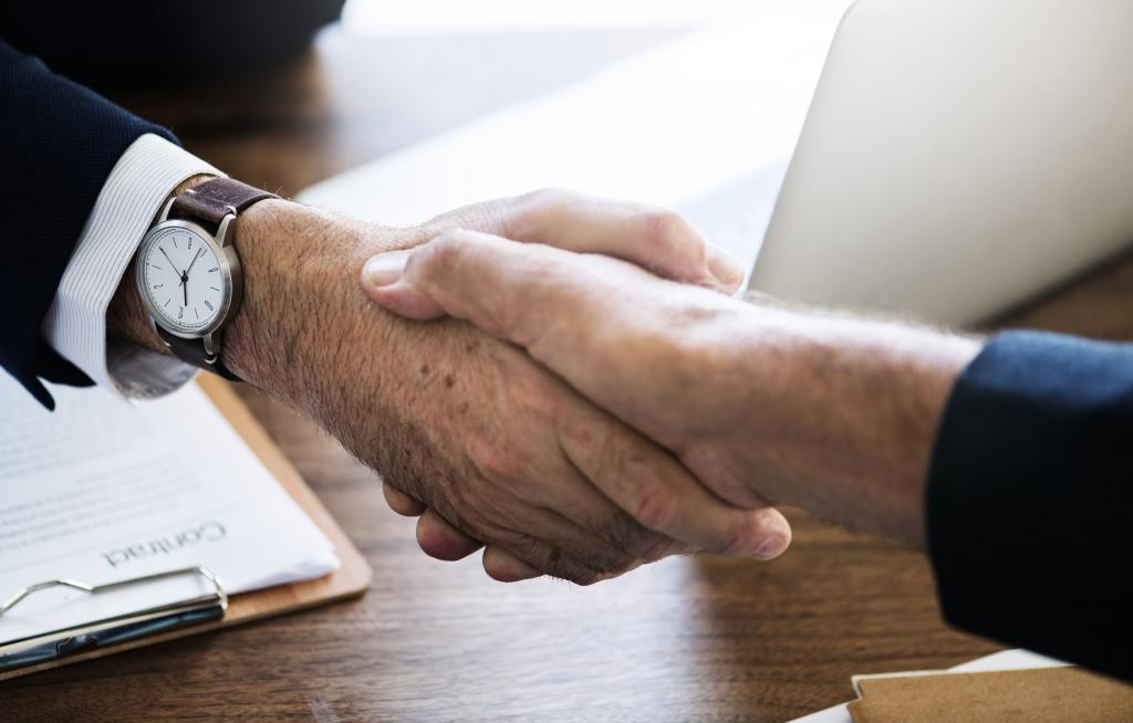 Deux personnes se serrant la main autour d'un contrat