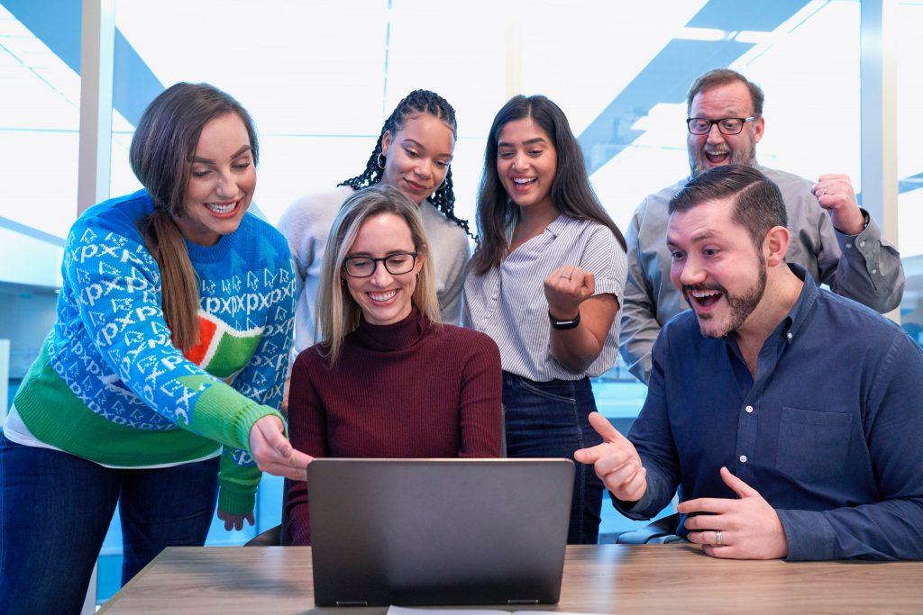 Étudiants rassemblés autour d'un ordinateur à la recherche d'un job